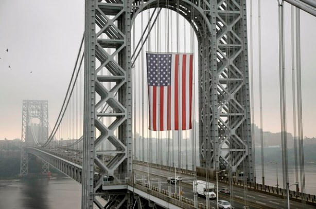 The largest free-flying American flag in the world flies over the George Washington Bridge Monday, Sept. 2, 2013, in Fort Lee, N.J. The Port Authority of New York and New Jersey says the flag will fly on Labor Day under the upper arch of the bridge's New Jersey tower. It's meant to honor working men and women across the country. The flag is 90 feet long by 60 feet wide, with stripes measuring about five feet wide and stars about four feet in diameter. (AP Photo/Mel Evans)