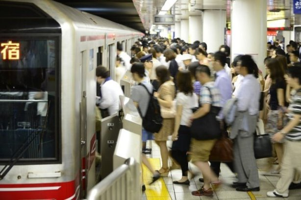 TO GO WITH Japan-transport-leisure-tourism-subway,FEATURE by Hiroshi HIYAMA This photo taken on July 12, 2013 shows people getting on a Marunouchi Line subway train during the morning rush hour at Ikebukuro Station in Tokyo.  The vast train network that criss-crosses subterranean Tokyo can be a confusing and intimidating place for the uninitiated. The city actually has two public subway operators: Tokyo Metro and Toei Subway, and between them they carry nearly 10 million passengers daily.           AFP PHOTO / Toru YAMANAKA
