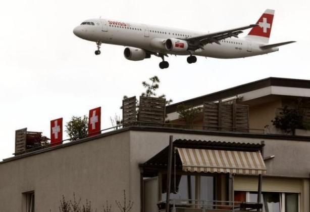 A jet of Swiss International Air Lines is seen behind an apartment building during its approach for a landing at Zurich Airport in the town of Kloten