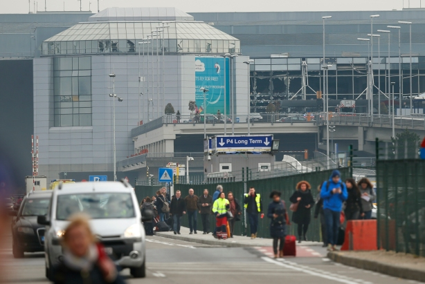 People leave the scene of explosions at Zaventem airport near Brussels, Belgium